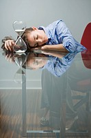 Businesswoman sleeping at table by hourglass