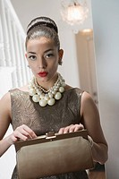 Young woman with pearls necklace holding purse and looking away