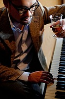 Mature Man Having a Drink and Playing Piano