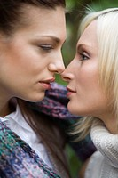 Portrait of two young women about to kiss