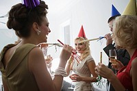 Portrait of young adult friends with party blowers and drinks at Christmas party