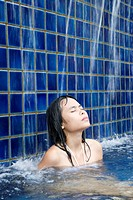 Woman in swimming pool at Dhevi Mandarin Oriental resort, Chiang Mai, Thailand                                                                        ...