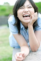 Young woman lying on bench laughing