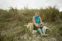 Woman at the coast with a book