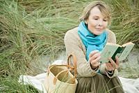 Woman at the coast reading a book