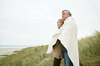 Mature couple outdoors, wrapped in blanket