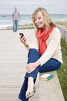 Woman at the coast with smartphone