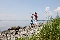 Father and son on beach with fishing rods (thumbnail)