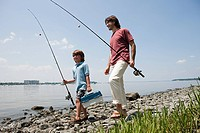 Father and son on beach with fishing rods
