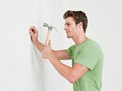 Young man hammering nail into wall