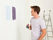 Young man with paint on wall