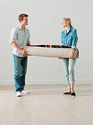 Young couple carrying a rolled up rug