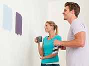 Young couple looking at paint on wall