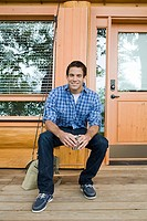 Young man sitting outside log cabin