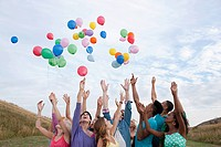Young people releasing balloons