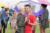 Young couple under umbrella at festival