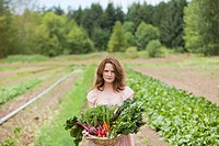 Young woman on farm with basket of vegetable produce