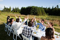 People raising glasses at dinner party on a farm