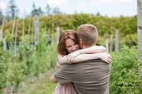 Couple hugging on a fruit farm
