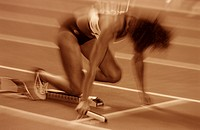Women relay race: athlete at the starting block ...