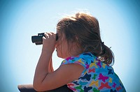 A young girl on her fathers shoulders watches the air show thru bionoculars