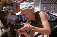 CAROL REICHMAN show a child her camera in a VILLAGE near MOREMI GAME RESERVE, OKAVANGO DELTA _ BOTSWANA