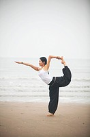 a woman doing Yoga in a seashore