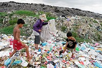 CAMBODIA  Scavenger Soun Srey Thouch searching for recyclable materials on Phnom Penh's Mean Caeay garbage dump, with sons Khoeun Sovan 8 and Khoeun S...