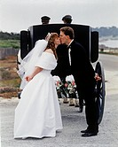 Bride & groom kiss behind a horse drawn carriage _