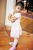 Little girl in ballet costume looking at camera.