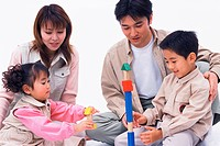 Parents looking on as their children play with toys