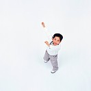 High angle view of a small boy with raised hands