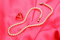 Jewellery in form pearl necklace with synthetic red gem stone of heart shape against pink satin background