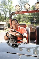 South Asian Indian young man sitting on driver´s seat in India jeep and holding steering wheel , India MR 703H