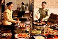 Girls preparing sweet pancakes and other desserts at the Oriental Hotel, Bangkok, Thailand