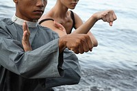 Man amd woman practicing Silat on beach