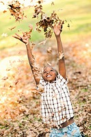 Boy 8_9 throwing autumn leaves up into air