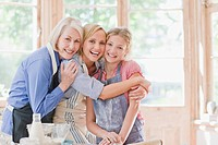 Smiling multi_generation females hugging in kitchen