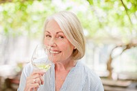 Smiling woman drinking white wine (thumbnail)