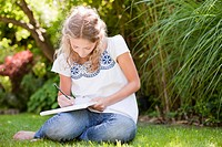 Girl sitting in grass and drawing on sketch pad