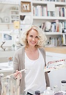 Smiling woman holding paintbrush and palette in art studio
