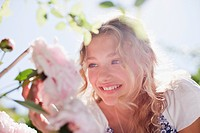 Smiling girl looking at pink flowers