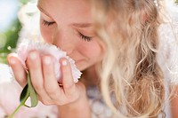 Close up of girl smelling pink flowers
