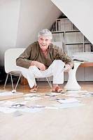 Smiling man looking at art items on floor
