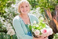 Smiling woman holding basket of flowers in garden