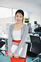 Smiling businesswoman holding laptop and folders in office