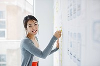 Smiling businesswoman placing adhesive note on whiteboard
