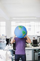 Businessman holding globe over face in office