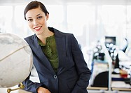 Smiling businesswoman next to globe in office (thumbnail)