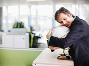 Smiling businessman hugging globe in office (thumbnail)